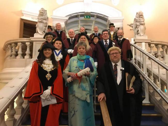 Marcelle Lloyd-Hayes flanked by Hereford City Council staff and members on the steps inside Hereford Town Hall.