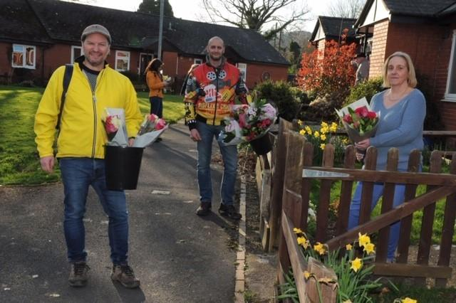 """From left Andy Bradley and Gary Baxter after giving a bunch of flowers to Paula Traylo in Kington. Picture by Andy Compton"