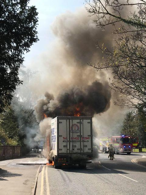 Ledbury Reporter: Firefighters tackle the lorry fire, which left a plume of black smoke rising into the air. Picture: Gino Beaumont