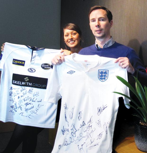 SIGNED SHIRT: Tania Parmar and Matthew Egginton, of Johnson Flemming, get ready for the charity auction.