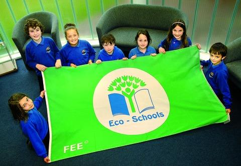 GREEN: From left, Isabella Bills-Geddes, 10, Callum Neville, 11, Olivia James, 11, Michael French, nine, Phoebe Rogers, nine, Georgia Fisher, 10, and Nathan  Moors, nine, with their Eco flag. 4712181801. Picture taken by Nick Toogood.