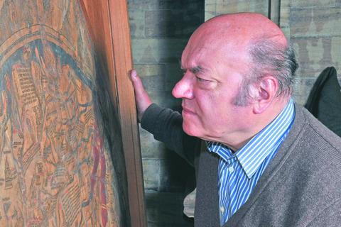 Chris Clarkson, a map conservation expert, inspects the Mappa Mundi at Hereford Cathedral