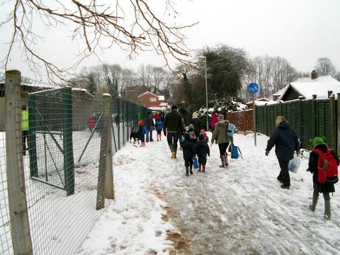 DETERMINATION: Parents and children trudge through the snow as they make their way to Ledbury Primary School.