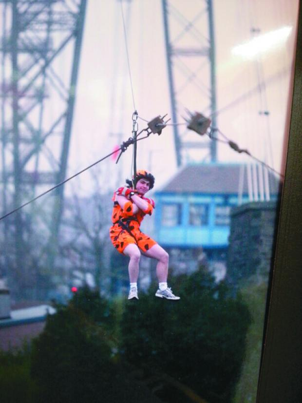 Andy Shough, from Whitecross, dressed as Fred Flintstone to descend the 74m landmark structure above the River Usk.