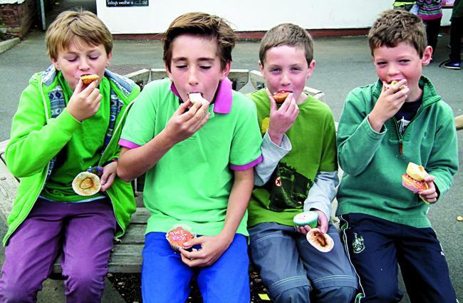YUMMY TIME: Downs School pupils get stuck in to coffee mornign treats. From left: Louis Packham, Jacob Perry, Peter Ingram and Antoine Sciater.