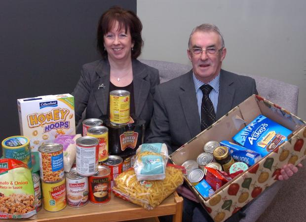 Ledbury Reporter: Senior funeral director Gill Stamp-Hedley with funeral conductor Roger Oliver with the food bank donations. Picture: James Maggs.