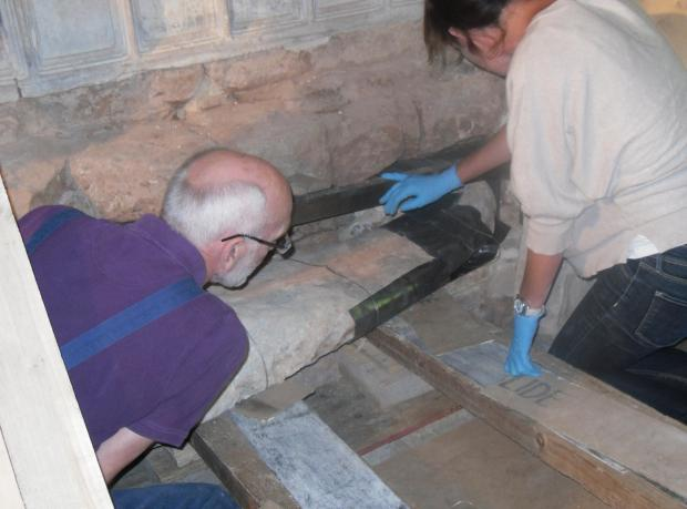 Ledbury Reporter: Conservator Michael Eastham (left) and Bianca Madden, a fellow conservator, work on the body found inside the memorial at St Bartholomew's Church at Much Marcle, near Ledbury.