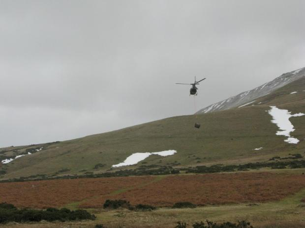 A helicopter flies up a one-tonne load of stone for the repairs.