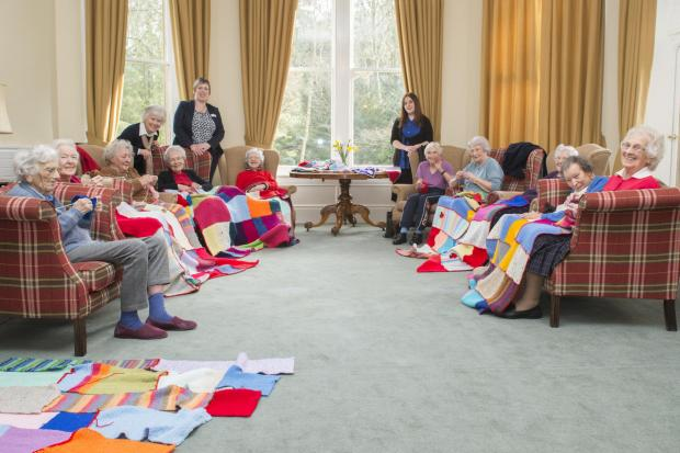 Members of Dulas Court's 'knit and natter' group knitting blankets for children in Nepal.