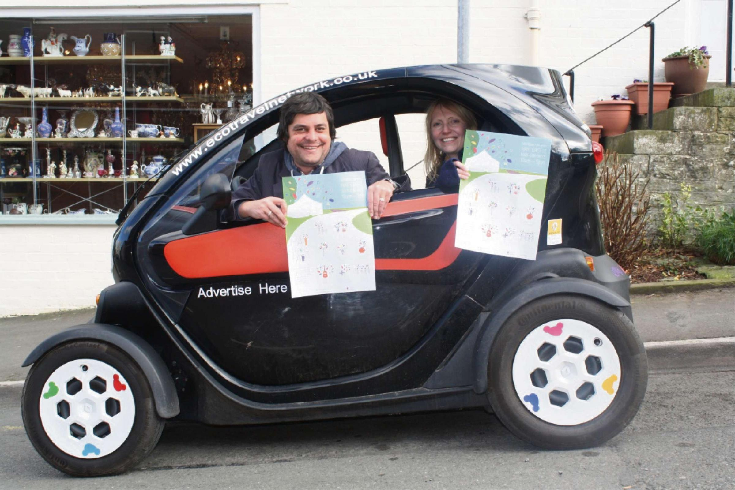 "Hay-on-Wye Spring Fair organisers distributing posters in a ""Twizy"" electric car from the Eco Travel Network."