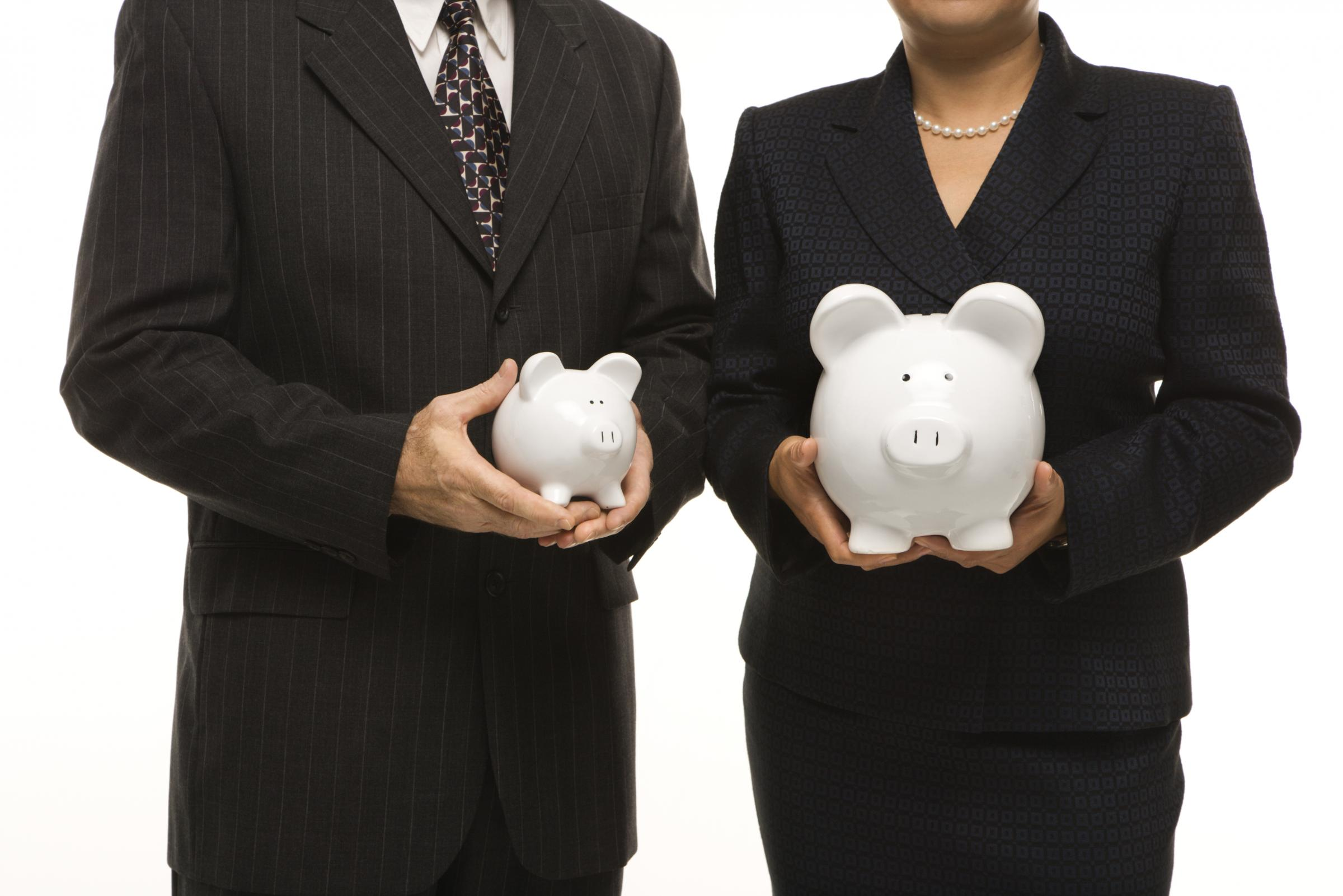 Caucasian middle-aged businessman and Filipino businesswoman holding different sized piggybanks. (7578556)