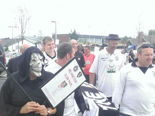 Hereford United fans carry coffin in a funeral procession through city to mark the club's 'death'