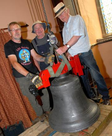 From left to right: Bell hanger Phil Dunnett and volunteers Paul Grey and Arthur Pearce with one of the restored bells ready to be hoisted in to the tower at the church of St Phillip and St James in Tarrington.  Picture by Nick Toogood. 2714639601