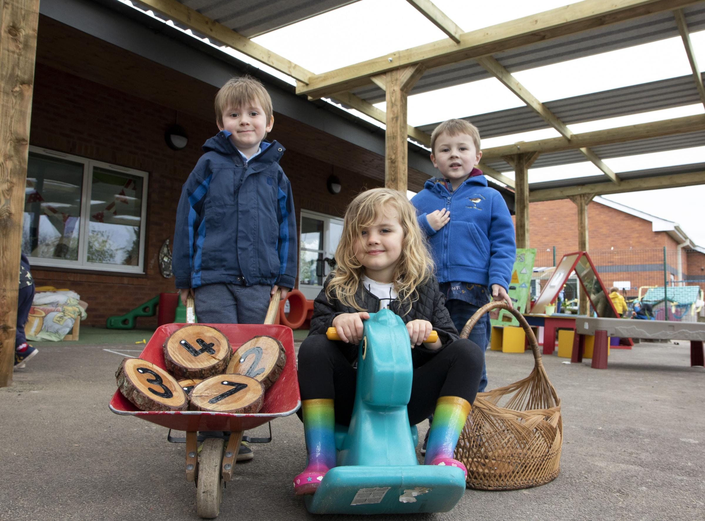 OUTDOOR FUN: Little Wrens Pre-school and Nursery have a new canopy over their outside play area. From left - Joey Fletcher, four, Matilda Arendz, three and Isaac Mitchell, four..